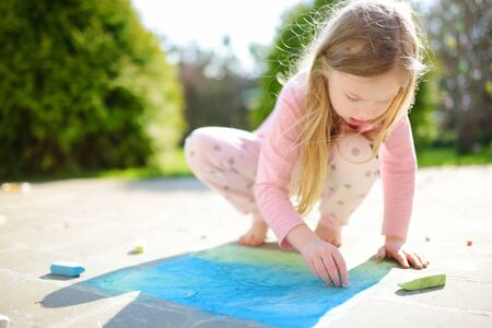 Cute little girl drawing with colorful chalks on a sidewalk. Summer activity for small kids. Creative leisure for family.