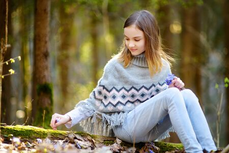 Adorable young girl picking the first flowers of spring in the woods on beautiful sunny spring day. Cute child having fun outdoors. Kid exploring nature. 写真素材