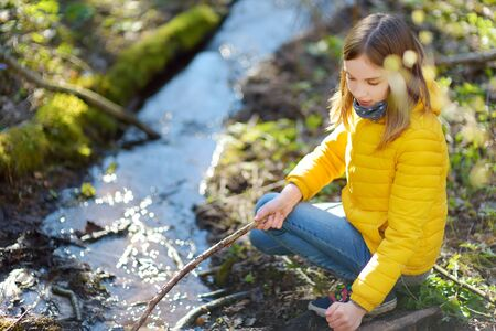 Cute young girl having fun by a river on warm spring day. Child playing by a water. Outdoor family activities in early spring.