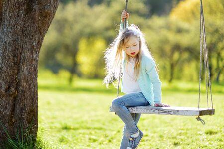 Cute little girl having fun on a swing outdoors in summer garden. Summer leisure for small kids.