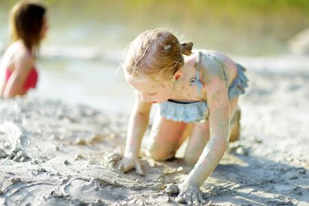 Young girl taking healing mud baths on lake Gela near Vilnius, Lithuania. Child having fun with mud. Kid playing with medicinal clay. Standard-Bild