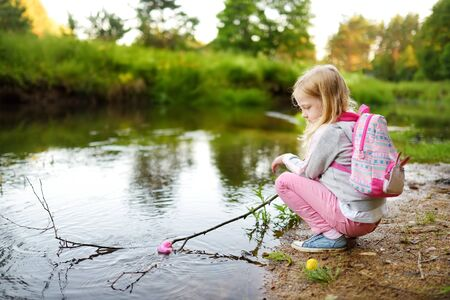 Cute young girl playing by a river with colorful rubber ducks. Child having fun with water on warm summer day. Active family leisure outdoors. Stock Photo