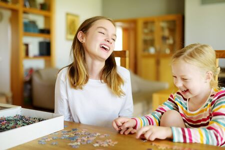 Cute young girls playing puzzles at home. Children connecting jigsaw puzzle pieces in a living room table. Kids assembling a jigsaw puzzle. Fun family leisure. Stay at home activity for kids.