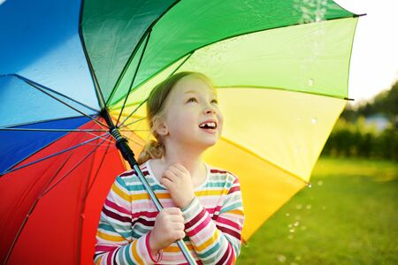Cute young girl holding colorful rainbow umbrella on rainy summer day. Child walking under warm rain outdoors. Outdoor summer activities for kids.