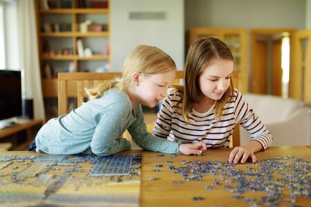 Cute young girls playing puzzles at home. Children connecting jigsaw puzzle pieces in a living room table. Kids assembling a jigsaw puzzle. Fun family leisure. Stay at home activity for kids. Imagens