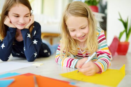 Two young sisters drawing with colorful pencils at home. Creative kids doing crafts together. Education and distance learning for kids. Homeschooling during quarantine. Stay at home entertainment. Banque d'images - 142794870