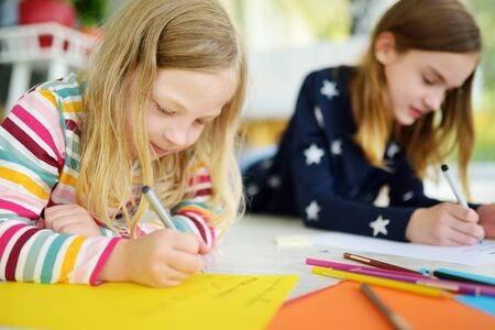 Two young sisters drawing with colorful pencils at home. Creative kids doing crafts together. Education and distance learning for kids. Homeschooling during quarantine. Stay at home entertainment. Banque d'images - 142794906