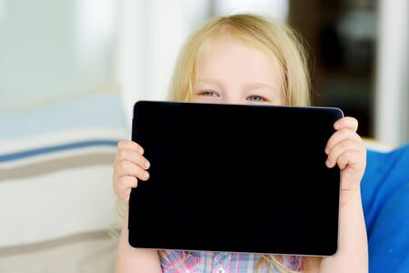 Smart little schoolgirl with digital tablet in at home. Child using gadgets to study. Education and distance learning for kids. Homeschooling during quarantine. Stay at home entertainment. Zdjęcie Seryjne