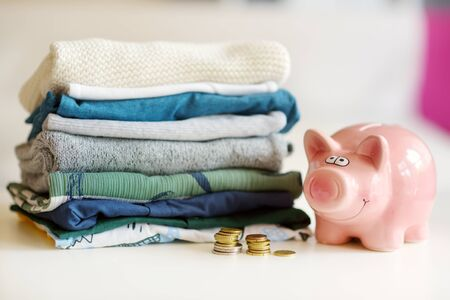 A pile of baby clothes, coins and a piggy bank. Parenting expenses concept. Working out a baby budget. Saving money when planning for a newborn. Budgeting for a new baby.