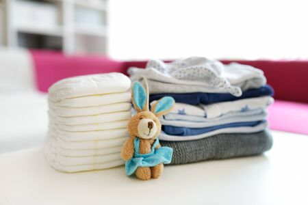 A pile of baby clothes, disposable diapers and a toy rabbit. Parenting expenses concept. Working out a baby budget. Saving money when planning for a newborn. Budgeting for a new baby. Imagens