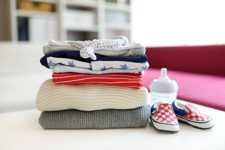 A pile of baby clothes, feeding bottle and little newborn shoes. Parenting expenses concept. Working out a baby budget. Saving money when planning for a newborn. Budgeting for a new baby. Imagens