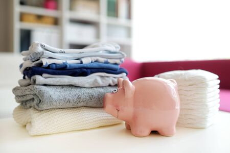 A pile of baby boy clothes, disposable diapers and a piggy bank. Parenting expenses concept. Working out a baby budget. Saving money when planning for a newborn. Budgeting for a new baby. Imagens