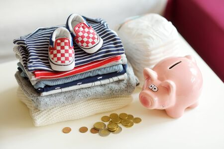 A pile of baby clothes, disposable diapers and a piggy bank. Parenting expenses concept. Working out a baby budget. Saving money when planning for a newborn. Budgeting for a new baby.