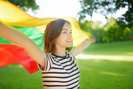 Cute young girl holding tricolor Lithuanian flag on Lithuanian Statehood Day. Child celebrating national holiday. 版權商用圖片