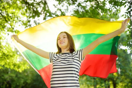 Cute young girl holding tricolor Lithuanian flag on Lithuanian Statehood Day. Child celebrating national holiday.