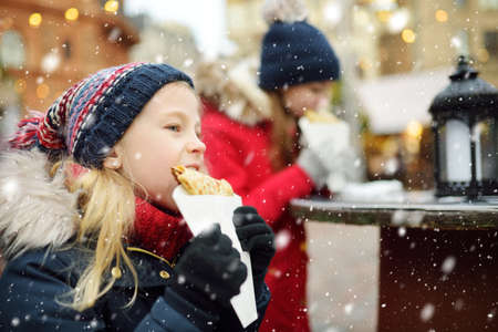 Cute young girls eating crepe pancake on traditional Christmas fair in Vilnius, Lithuania. Children enjoying sweets, candies and gingerbread on Xmas market. Winter time with family and kids.