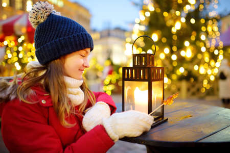 Cute young girl looking at a lantern on traditional Christmas fair in Riga, Latvia. Children enjoying sweets, candies and gingerbread on Xmas market. Winter time with family and kids.