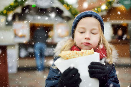 Cute young girl eating crepe pancake on traditional Christmas fair in Vilnius, Lithuania. Child enjoying sweets, candies and gingerbread on Xmas market. Winter time with family and kids. 版權商用圖片
