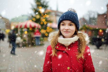Cute young girl having fun on traditional Christmas fair in Riga, Latvia. Children enjoying sweets, candies and gingerbread on Xmas market. Winter time with family and kids. 版權商用圖片