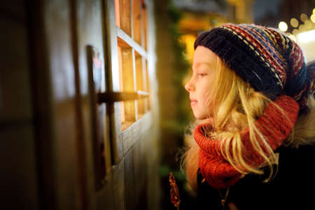 Adorable girl peeking through the window on traditional Christmas fair in Riga, Latvia. Winter time with family and kids.
