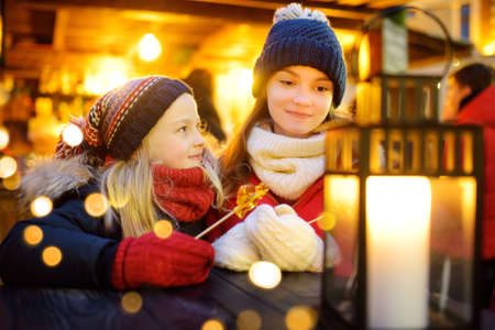 Two adorable sisters having rooster-shaped lollipops on traditional Christmas fair in Riga, Latvia. Children enjoying sweets, candies and gingerbread on Xmas market. Winter time with family and kids.