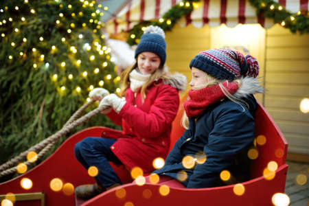 Two adorable sisters sitting having fun together on traditional Christmas fair in Riga, Latvia. Winter time with family and kids.