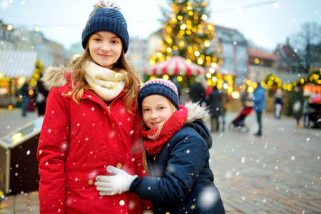 Two adorable sisters having a good time together on traditional Christmas fair in Riga, Latvia. Children enjoying sweets, candies and gingerbread on Xmas market. Winter time with family and kids. 版權商用圖片
