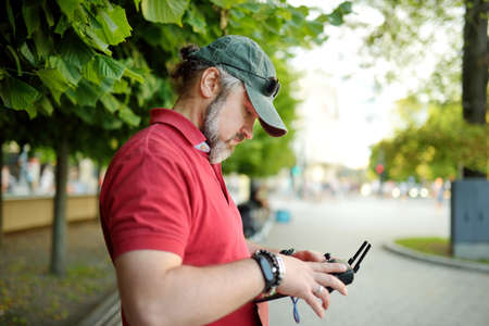 Man watching and navigating a drone. Bearded man operating the drone by remote control.