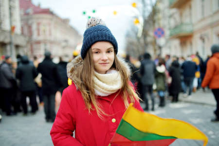 Cute young girl celebrating Lithuanian Independence Day holding tricolor Lithuanian flag in Vilnius, Lithuania