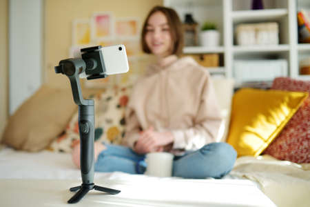 Beautiful teenage girl recording video blog with her smartphone. Young vlogger shooting vlog at home. Teen influencer creating content for her social media account. Social media and blogging concept.