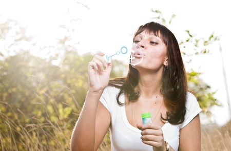 Young beautiful girl blowing bubbles outdoors  photo