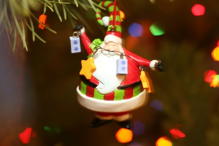 santa claus christmas decoration on fur tree with lights photo
