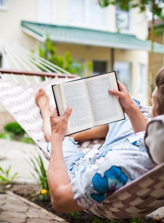 hamaca: Inhammock hombre swinging lee un libro Foto de archivo