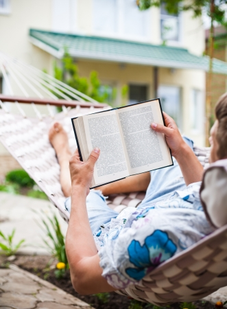 Man swinging inhammock reads a book