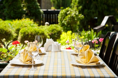 the place is outdoor: Outdoor restaurant dining table. Place setting