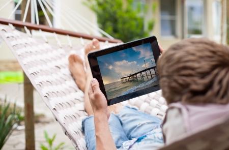 Der Mensch mit einem Tablet-Computer beim Entspannen in der H�ngematte Lizenzfreie Bilder