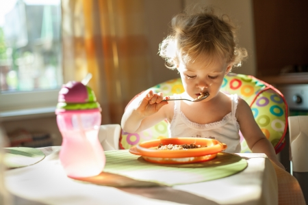 baby eating: Little baby girl eating breakfast. Beautiful natural light Stock Photo