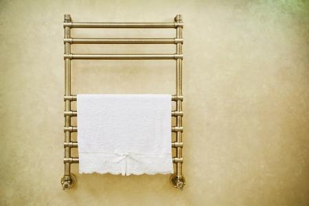 Modern heated towel rail on  bathroom wall.  Stock Photo