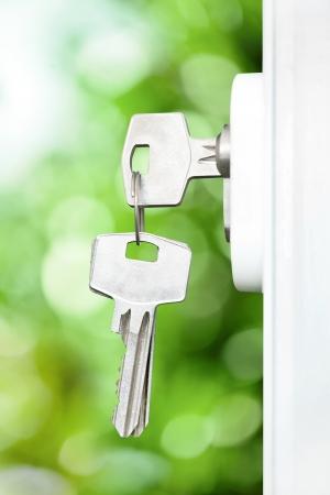 Keys in door lock, summer defocus background Stock Photo