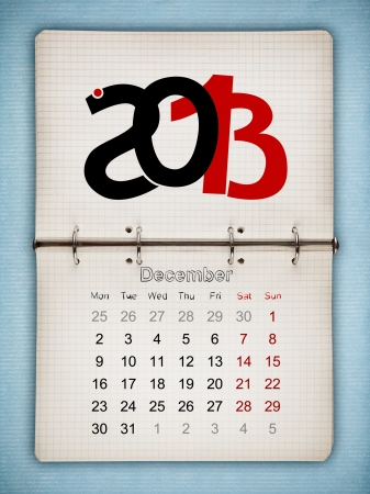 December 2013 Calendar, open old notepad on blue paper photo