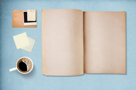 Coffee cup, note paper and notebook, vintage blue paper on background photo