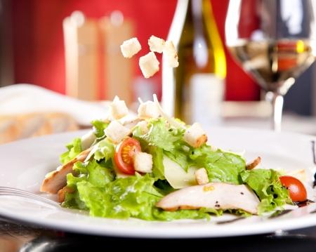 legumbres secas: Ensalada de pollo con verduras y trocitos de pan, una botella de vino en el fondo
