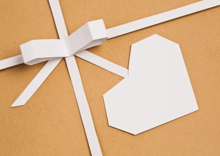 Hand made ribbon with bow and heart on kraft paper as background. Greeting card photo
