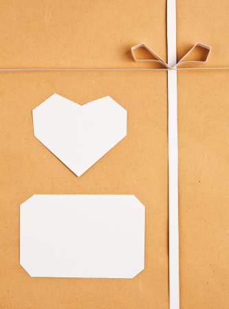Hand made paper tag and heart on kraft paper as background. Greeting card photo