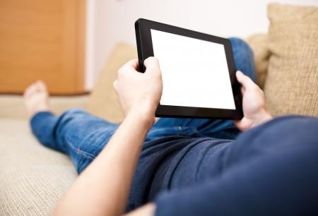 Man entspannend mit Tablette, die Verlegung auf Sofa