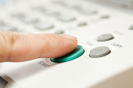photocopier: Office life, hand pressing start button on fax, copy machine  Stock Photo
