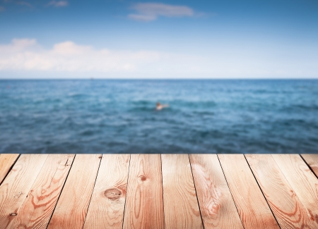 deck: Empty wooden table with blur sea on background.