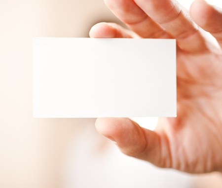 Human hand holding blank business card with copy space, small dof photo