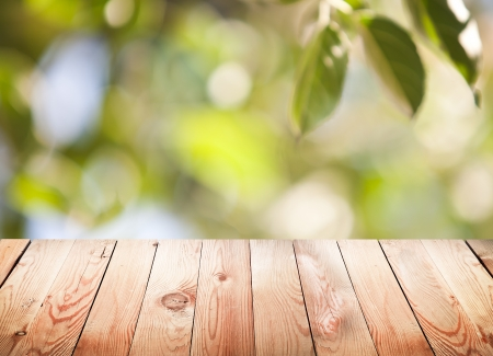 Empty wooden table with foliage bokeh background. Banco de Imagens