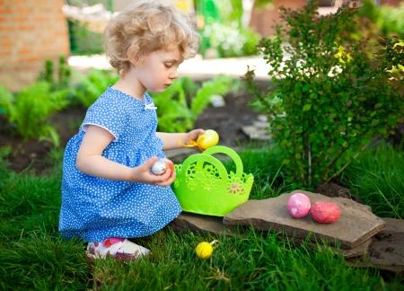 easter egg hunt: Little Girl on an Easter Egg hunt on a meadow in spring